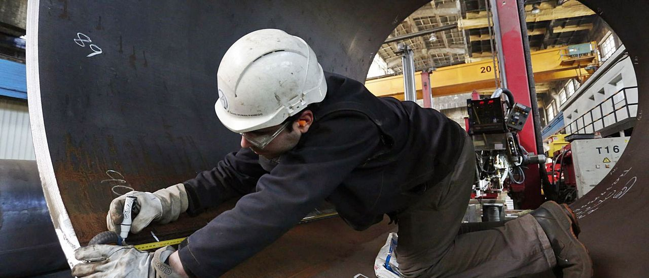 David Román, empleado de una empresa metalúrgica avilesina, marca una pieza para su posterior soldadura.