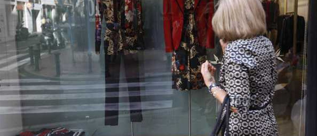 Una mujer mira un escaparate de una tienda de ropa en el centro de Alicante.