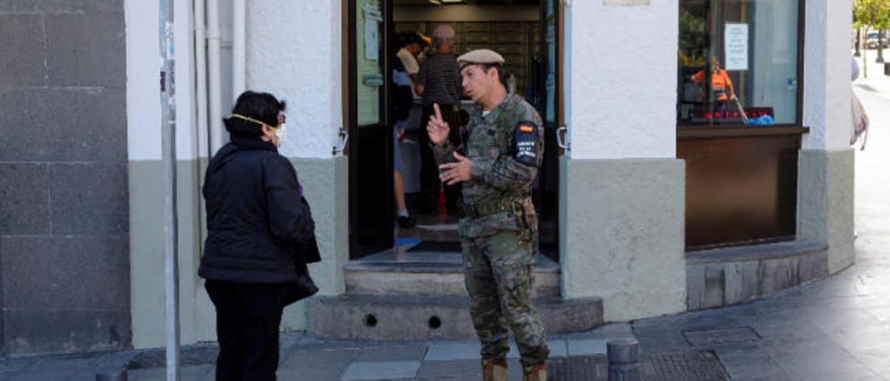 Un militar informa, ayer, a una grancanaria de las instrucciones de acceso a un edificio público.