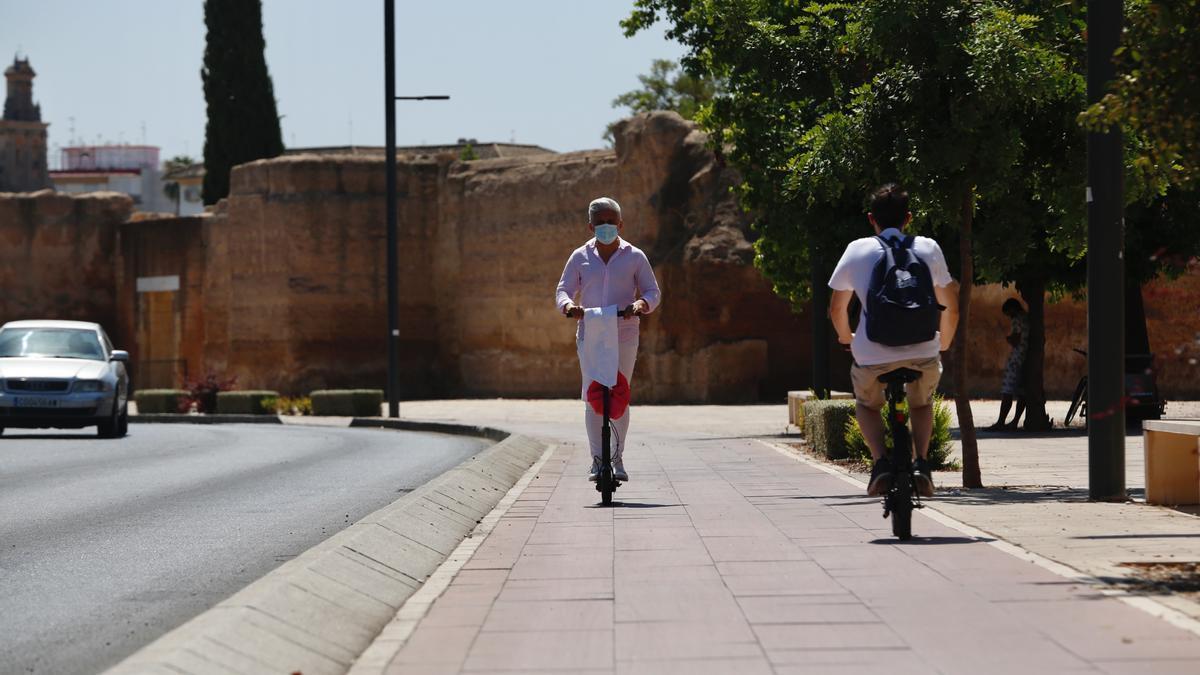 Un usuario de un patinete eléctrico y un ciclista circulan por el carril bici de ronda del Marrubial.