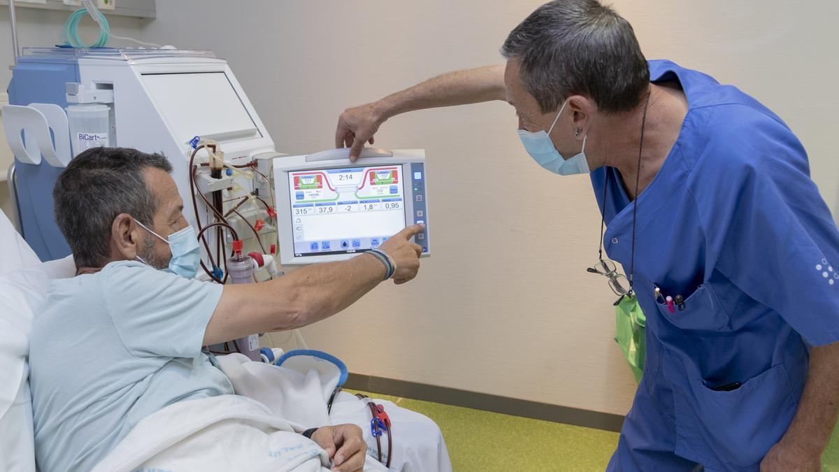 Un sanitario explica el uso del aparataje a un paciente en hemodiálisis