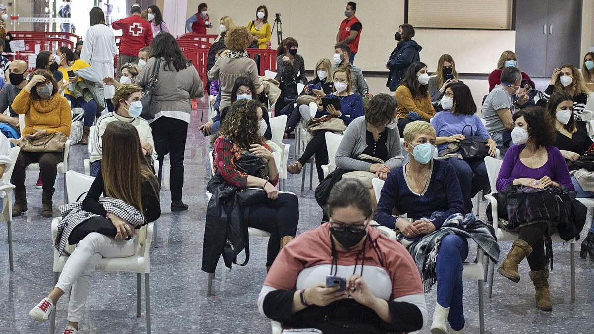 Un grupo de docentes de la comarca aguarda los quince minutos de rigor tras recibir la vacuna ayer en Alzira. | PERALES IBORRA