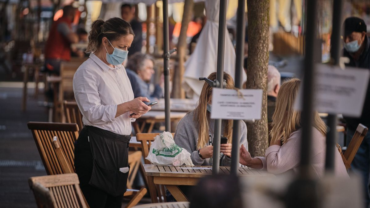 Una camarera atiende a unas clientas en una terraza.
