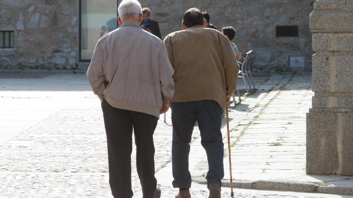 Dos hombres pasean por una calle.