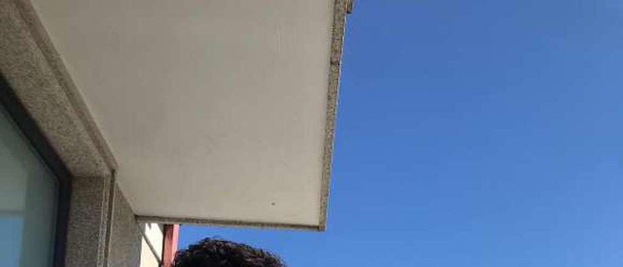 Ayoub Atib en el balcón de su piso en Cangas. // FDV