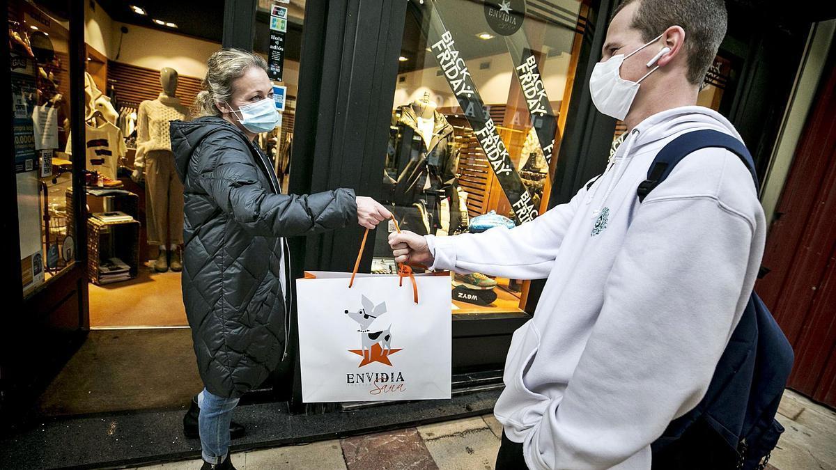 La comerciante Soledad Morté entrega un paquete a un cliente a la puerta de su tienda en Oviedo, ayer. | Irma Collín