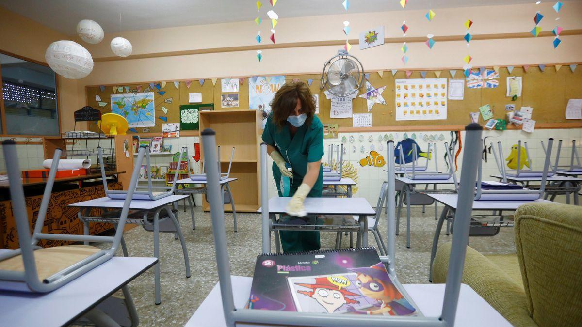 Una limpiadora prepara un aula de un centro escolar para la vuelta a clase hoy.