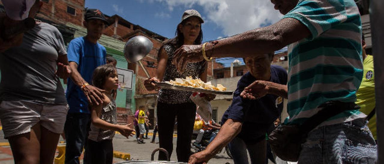 Varios vecinos de un barrio de Caracas se organizan para compartir un sancocho en septiembre del año pasado.