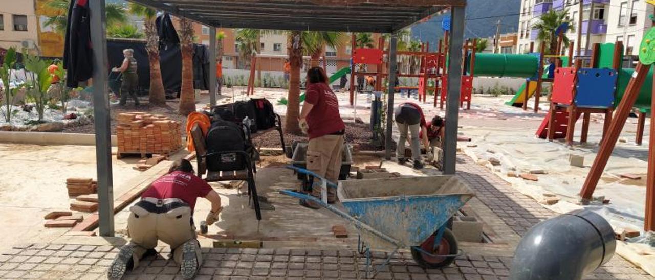 Varias alumnas de la especialidad de obra colocan pavimento bajo una de las pérgolas.   T. Á.C.