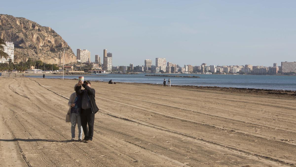 Una pareja se hace un selfi en la playa del Postiguet (Alicante)