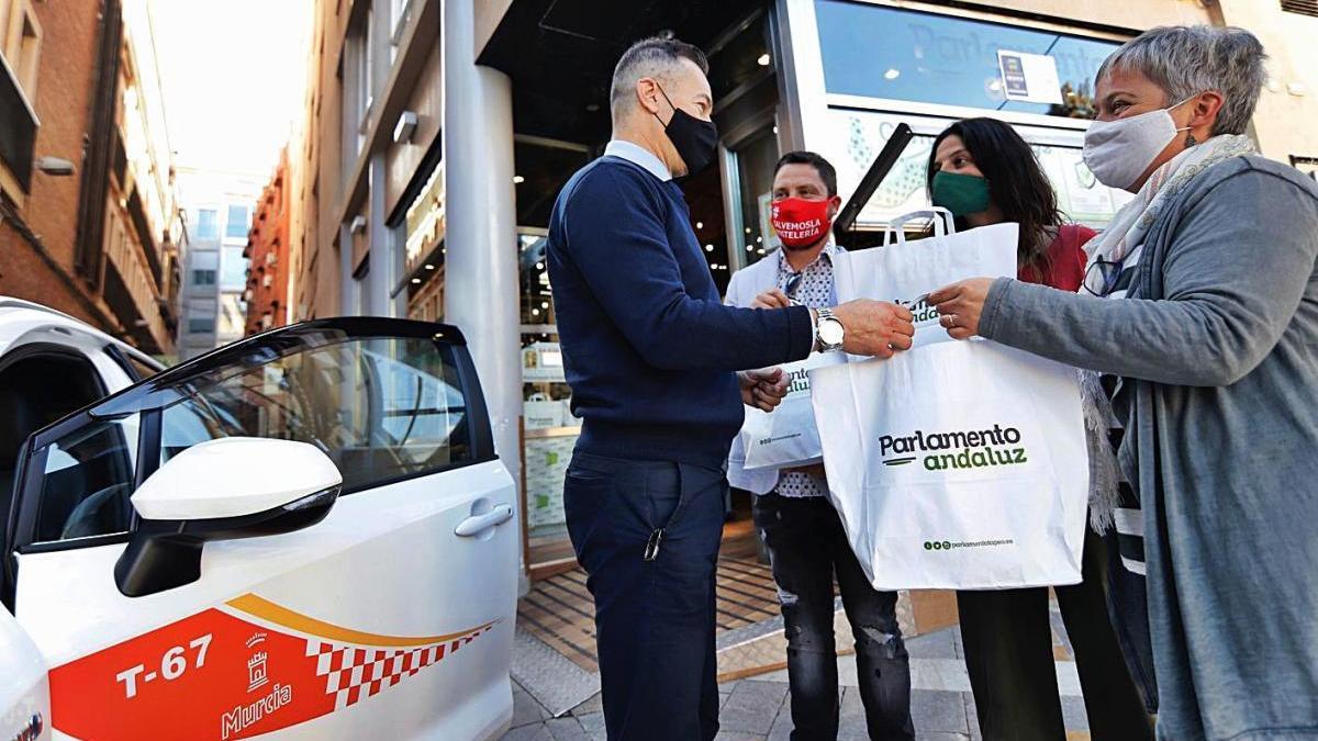 Un taxista reparte ayer comida a unos clientes en la plaza Romea de Murcia.