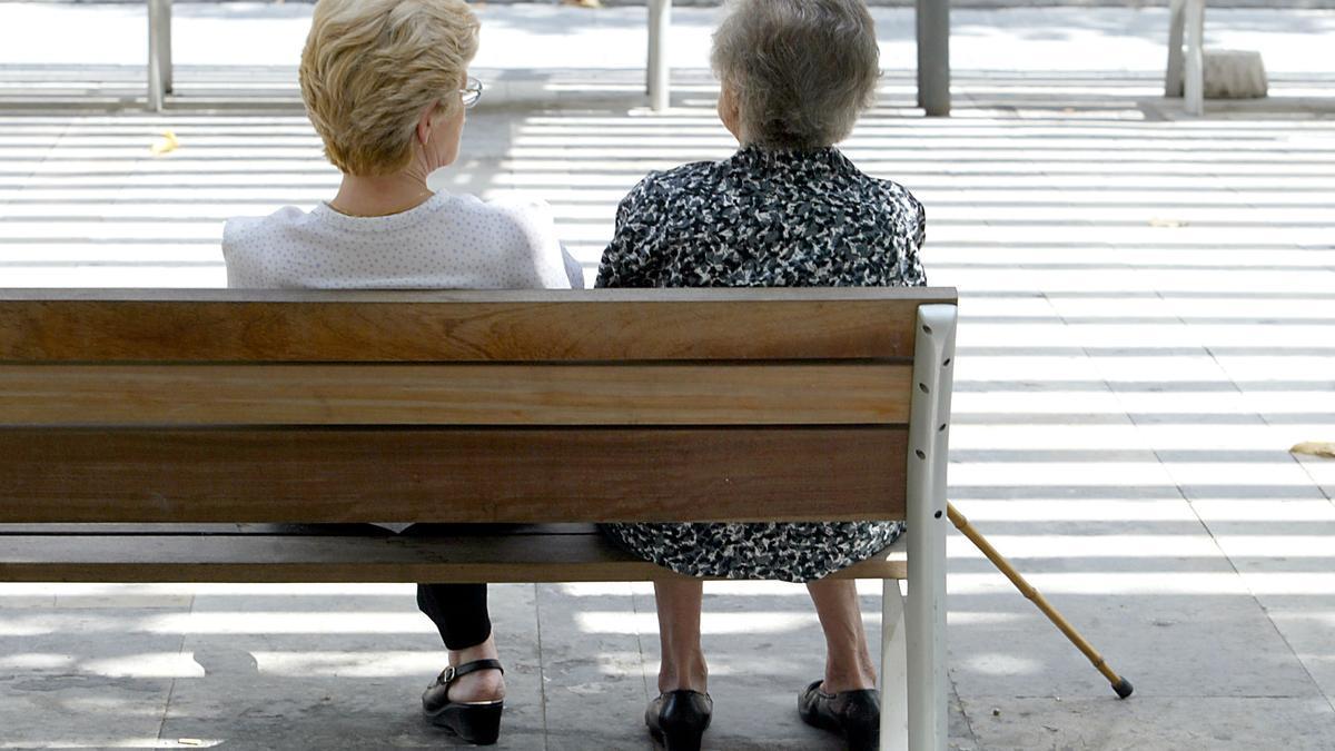 Dos mujeres mayores conversan en un banco.