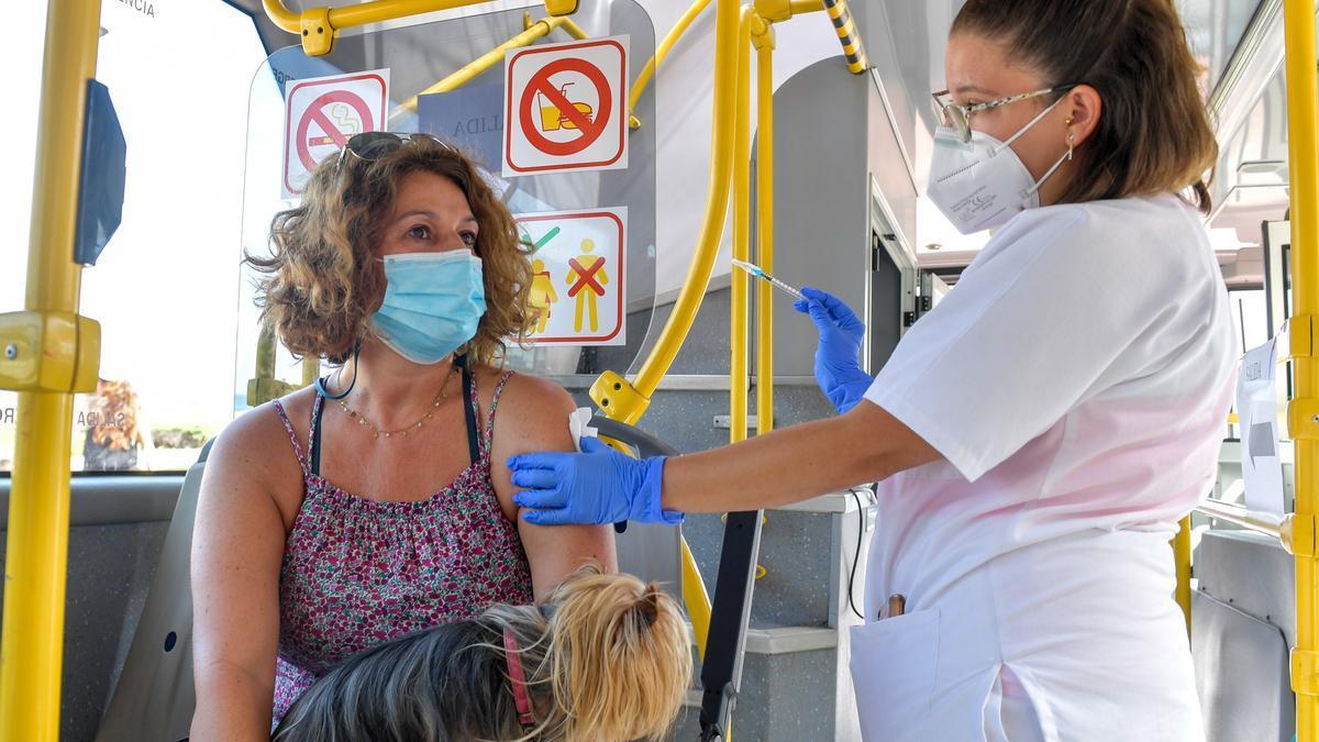 Una sanitaria vacuna a una mujer en la Vacuguagua en Las Palmas de Gran Canaria.