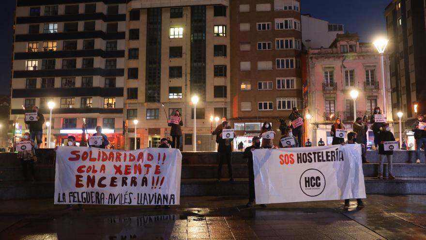 Los hosteleros gijoneses prenden bengalas en apoyo de los compañeros encerrados