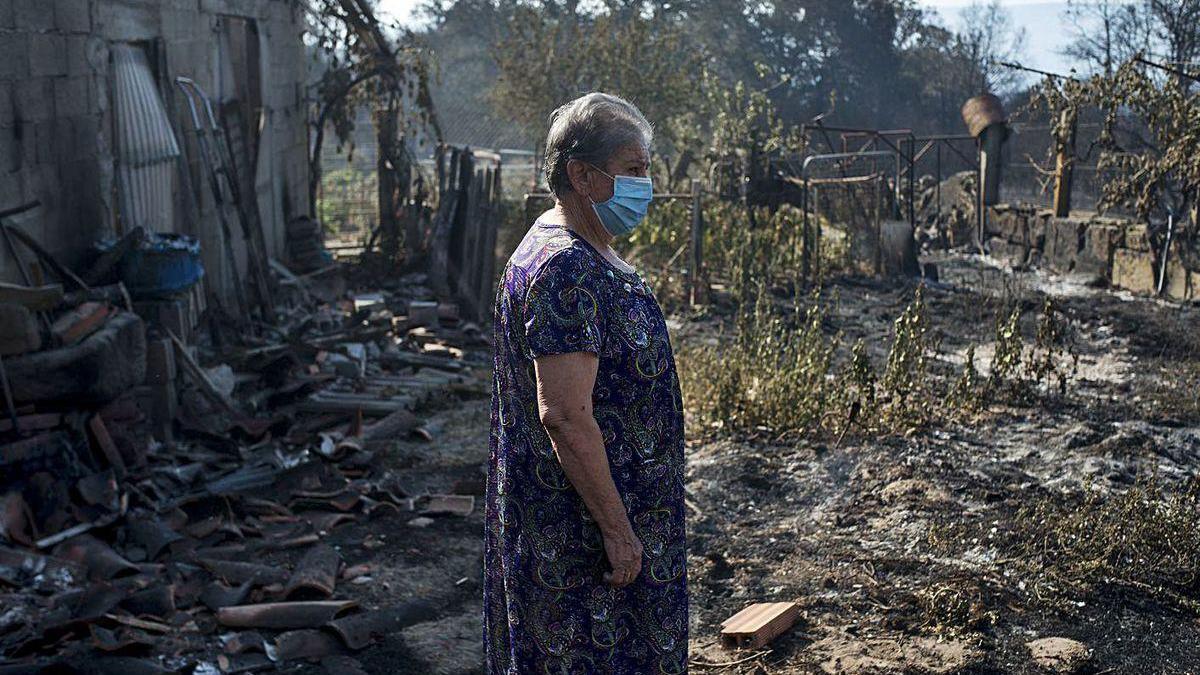 Una mujer inspeciona la finca con un alpendre arrasada por las llamas en San Cristovo (Monterrei).