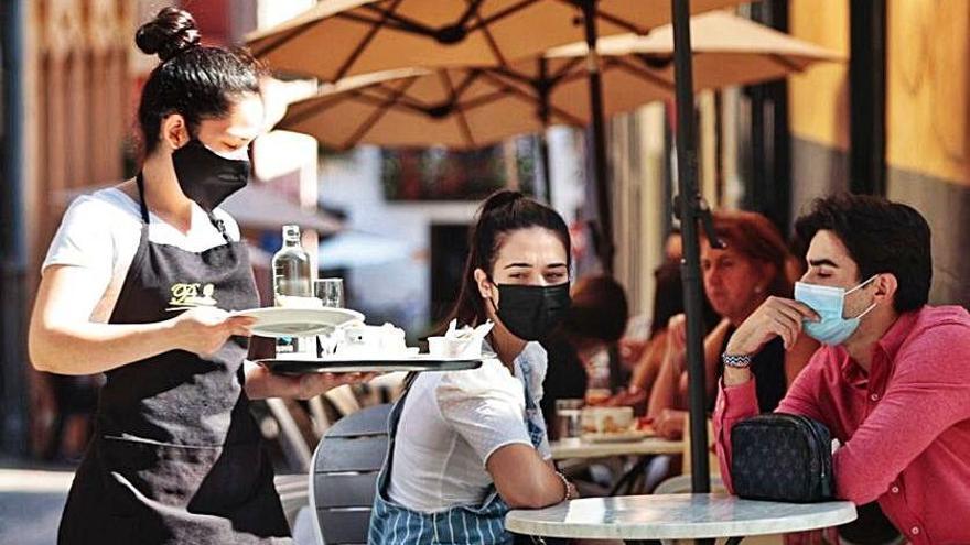 Una camarera atiende a los clientes de la terraza.