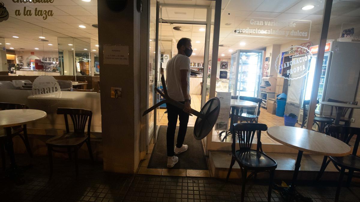 El responsable de una cafetería retira el mobiliario de la terraza poco antes de las 22.00 horas