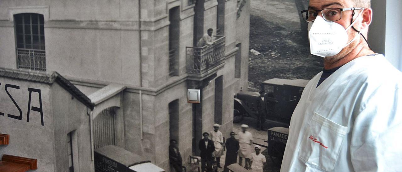 Marino García, ante una foto de gran tamaño de la panadería antigua de La Luarquesa, imagen que preside la entrada de las nuevas instalaciones, ubicadas en el polígono de Barcia-Almuña. | A. M. Serrano