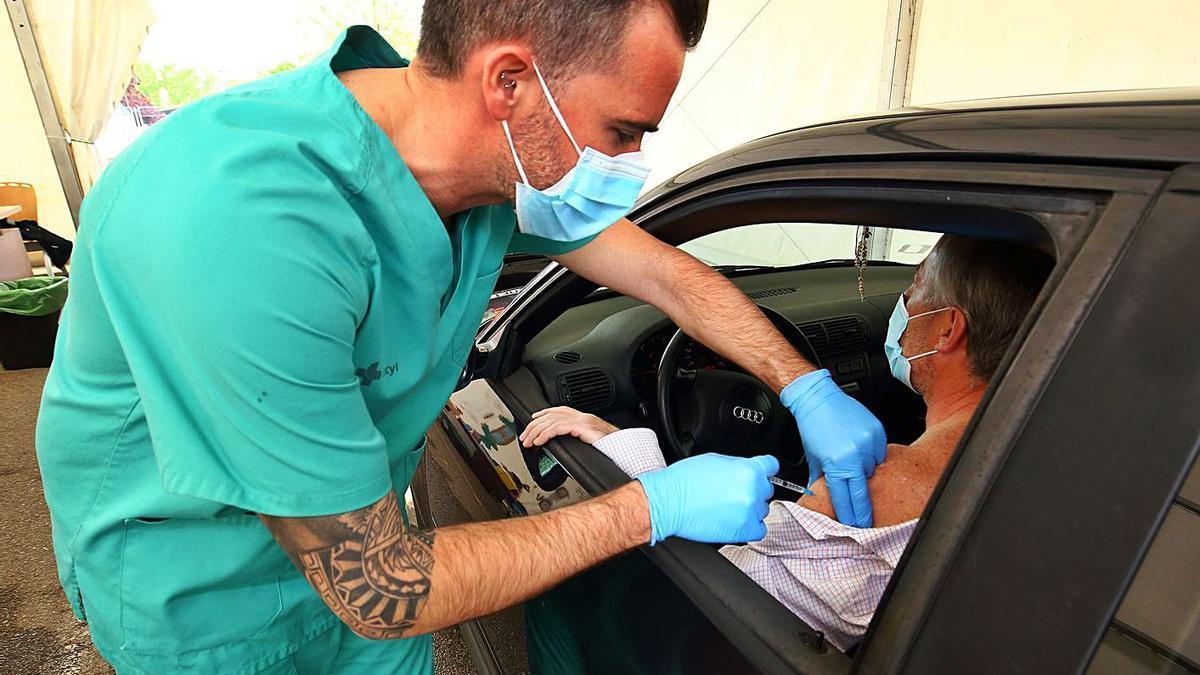 Un sanitario inyecta un vial durante la vacunación masiva en las comarcas del Bierzo y Laciana (León). | Ical