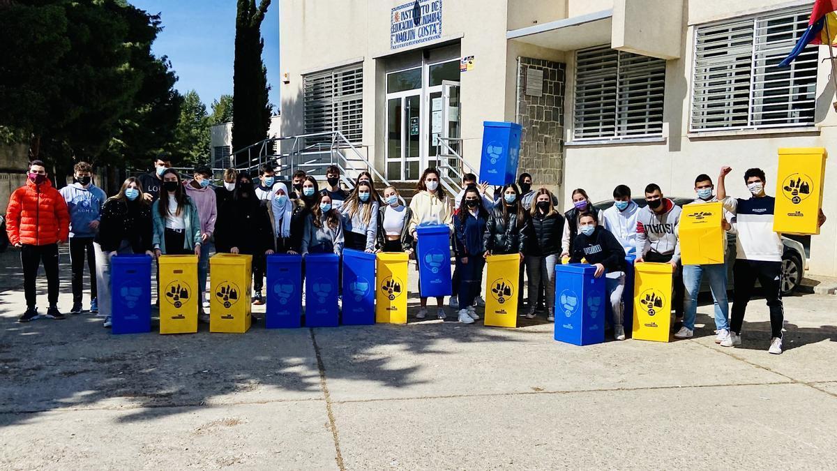 Los estudiantes del IES Joaquín Costa de Cariñena con los cubos de recogida selectiva de residuos para fomentar el reciclaje en el centro.