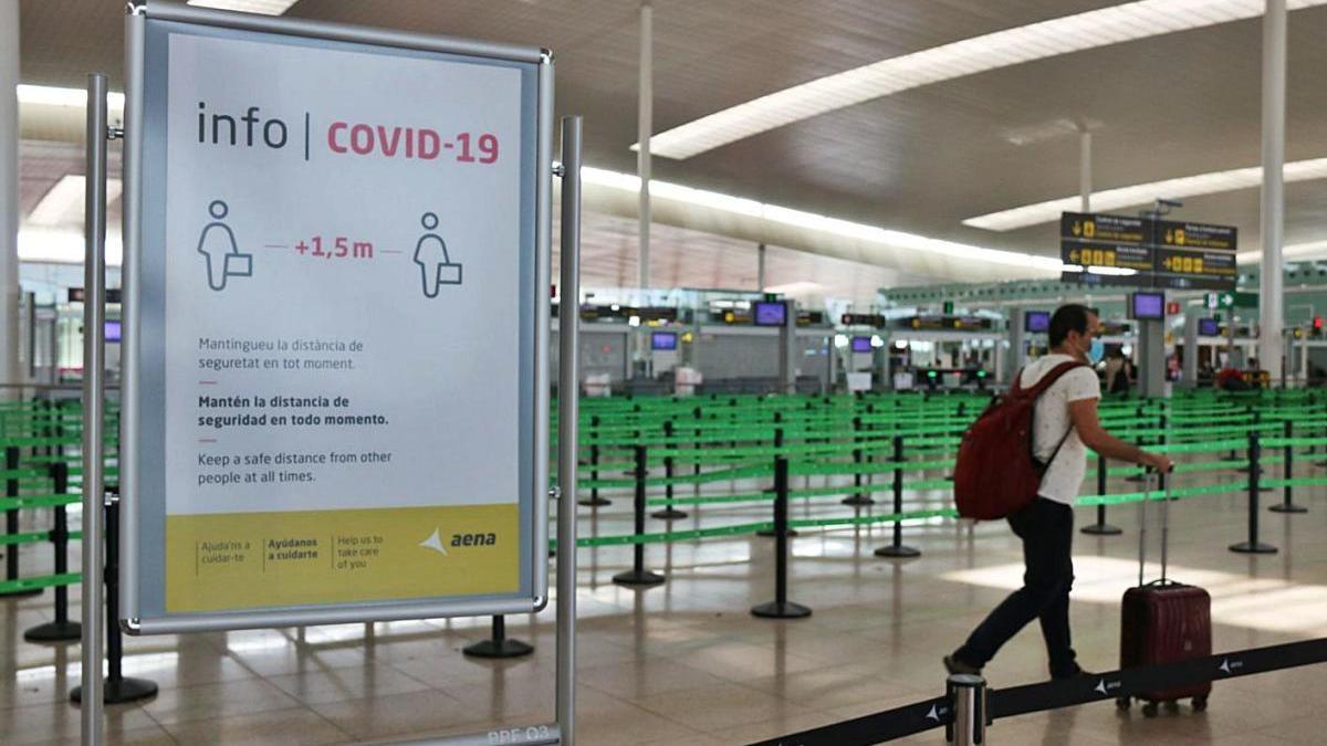 Un viatger passant per davant d'un cartell amb les restricions per la covid-19