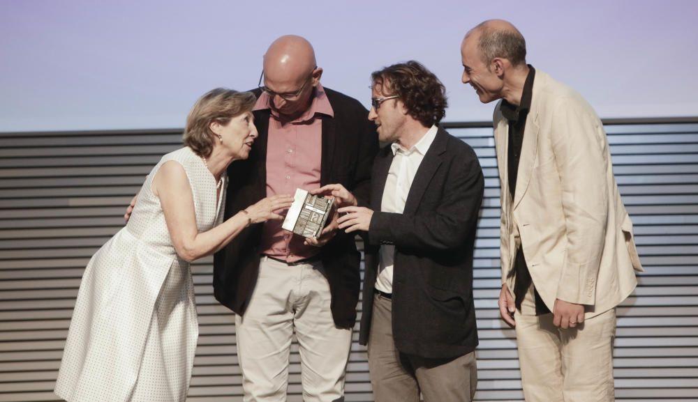 Montse Fuster, presidenta de Amadip Esment, entrega el premio a los representantes de 3Salut Mental -Alfons Suárez, Guillem Febrer y Miquel Bauça-.