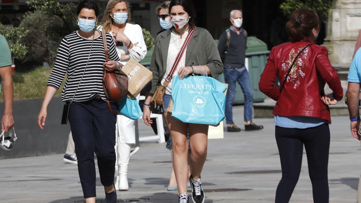Viandantes con mascarilla por el centro de Vigo. // J. Lores