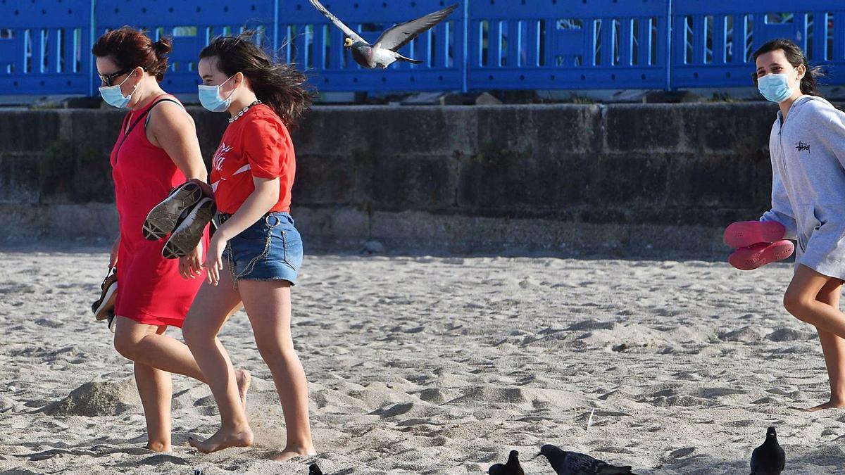 Tres mujeres, paseando por la playa con la mascarilla puesta el verano pasado.