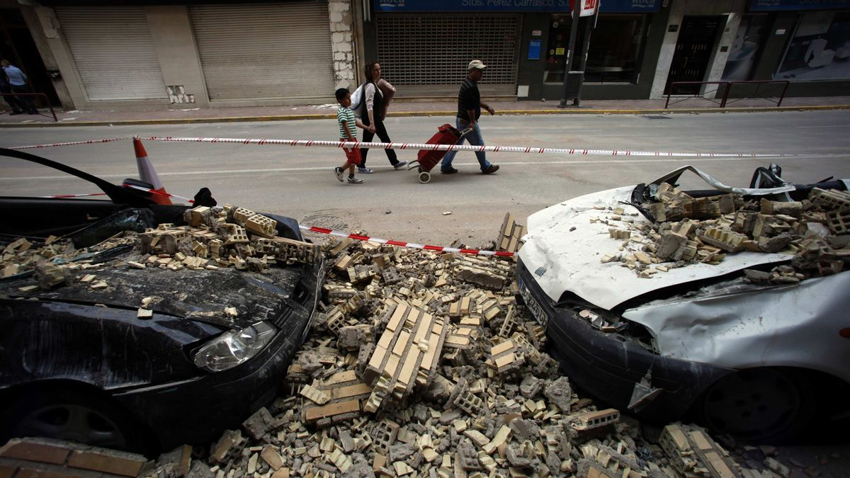 Vecinos de Lorca pasan por delante de una construcción derruida tras los temblores.
