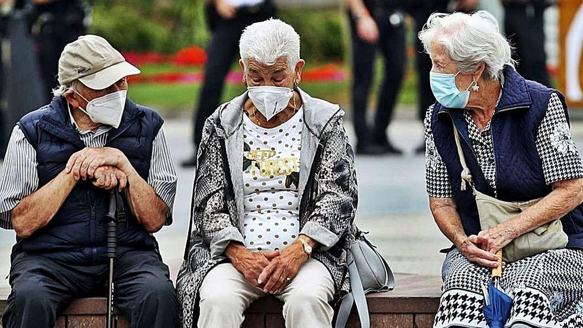 Persones grans parlant entre elles amb mascareta. | JUAN HERRERO