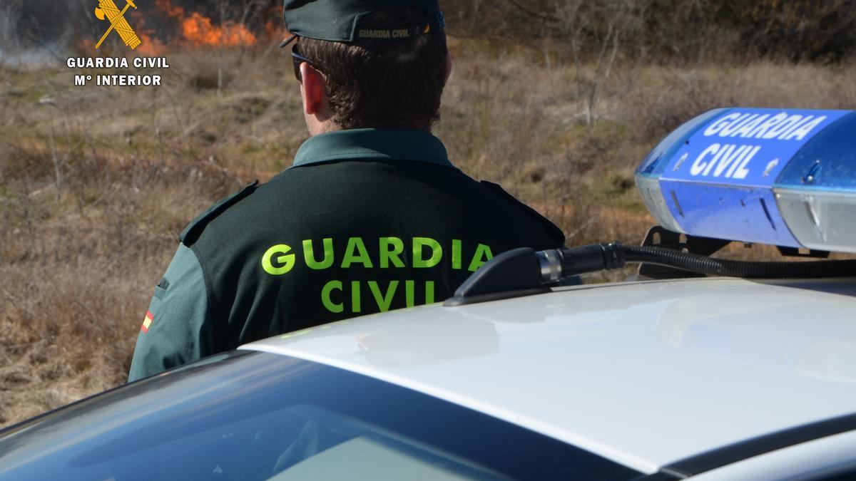 Un guardia civil vigila un incendio forestal.