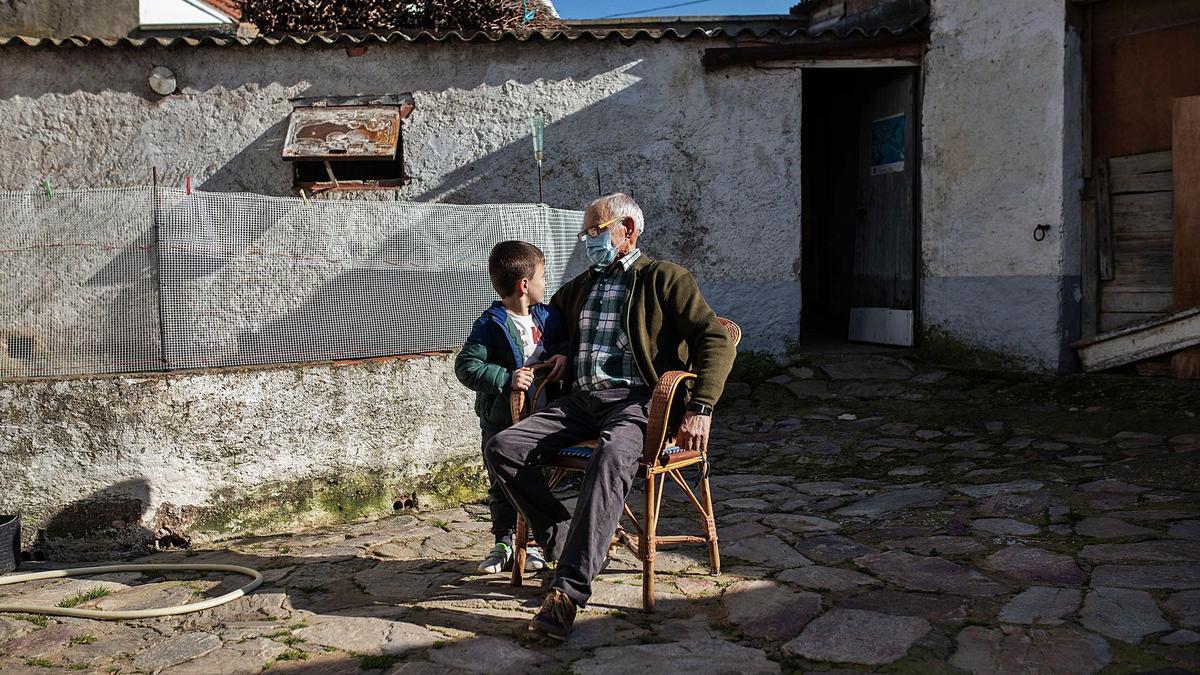 Ramiro Fernández Miguel, junto a su nieto Marco, en el corral situado en su domicilio de la localidad zamorana de Montamarta.