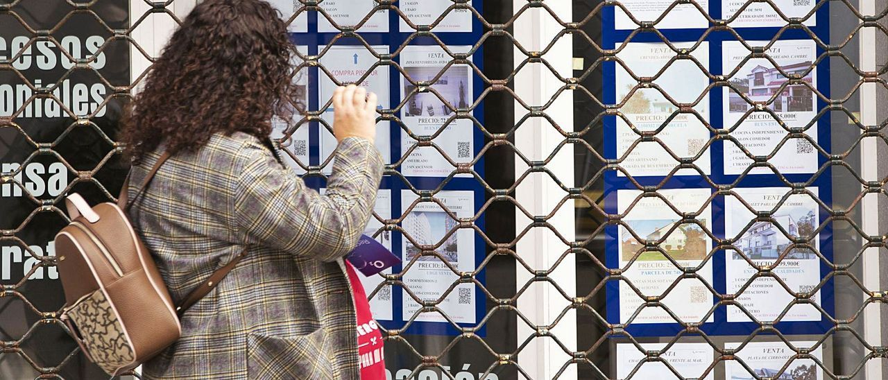 Una viandante observa la oferta de inmuebles en venta de una inmobiliaria. |   // MIGUEL MIRAMONTES