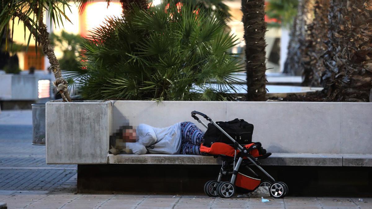 Una mujer duerme en un banco de hormigón de la plaza Mariano Arregui de Zaragoza, esta semana.