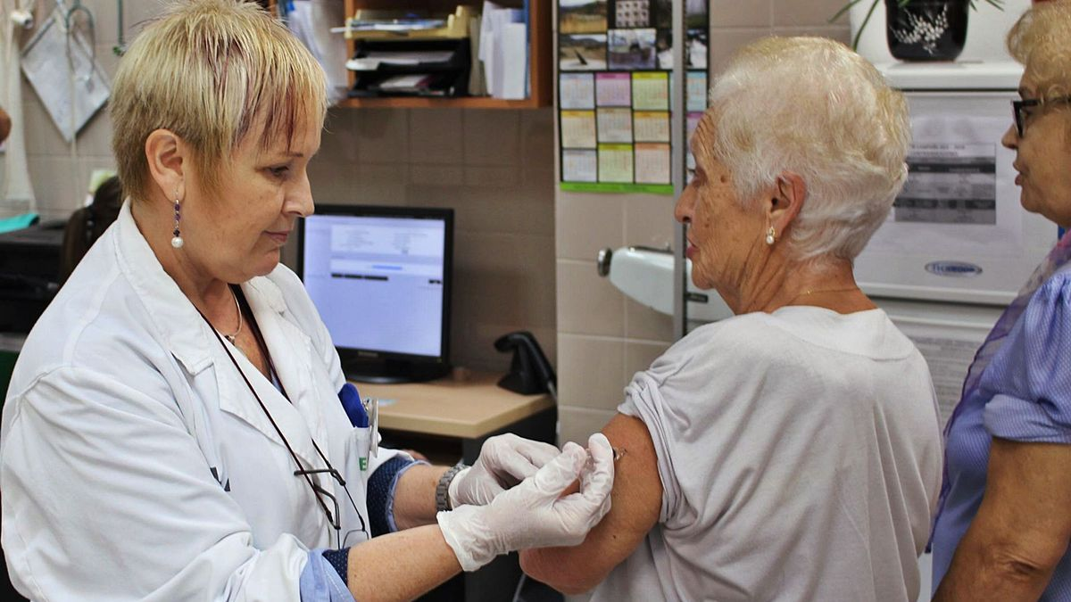 Una sanitaria vacuna contra la gripe a una mujer en un hospital. | LEVANTE-EMV