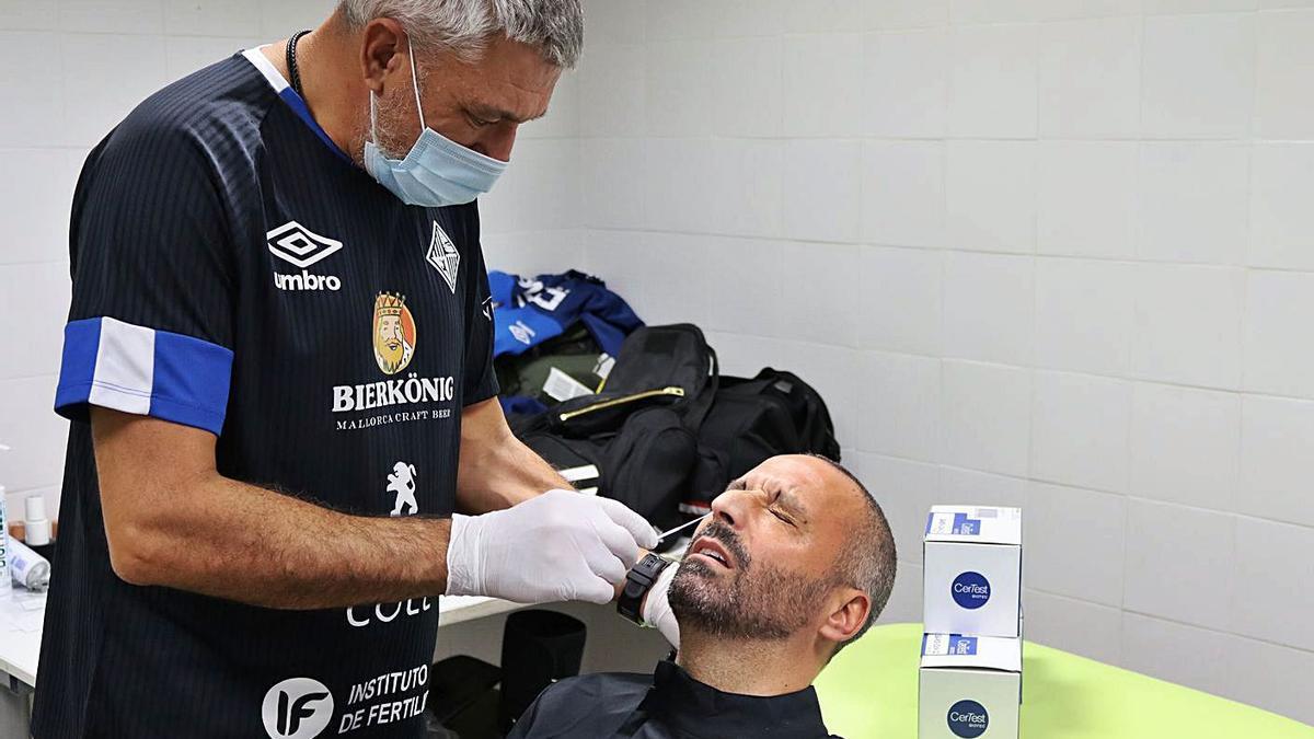 El doctor Miquel Mas realiza el PCR al técnico del Palma Futsal, Antonio Vadillo.