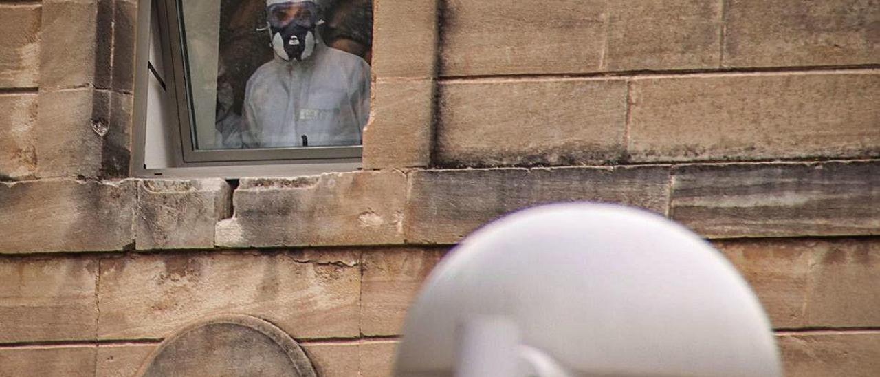 Un trabajador, ataviado con equipos de protección, se asoma a una ventana de la residencia de Oliver en el momento álgido del brote.
