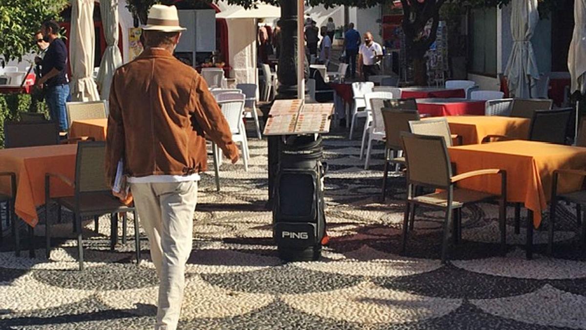 Un hombre pasea entre mesas vacías en la plaza de Los Naranjos.