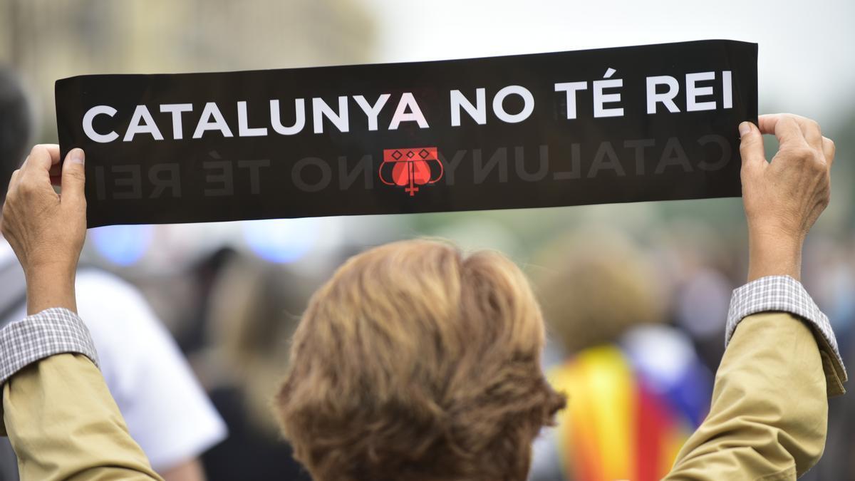 """Una mujer sostiene una pancarta donde se puede leer """"Cataluña no tiene Rey""""."""
