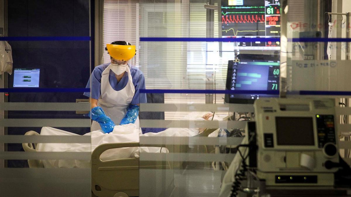 Una sanitaria atiende a un paciente con covid en la UCI