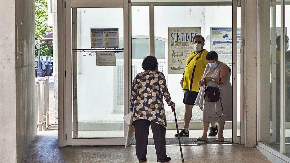 Una mujer y un hombre salen de un centro de salud de la ciudad.