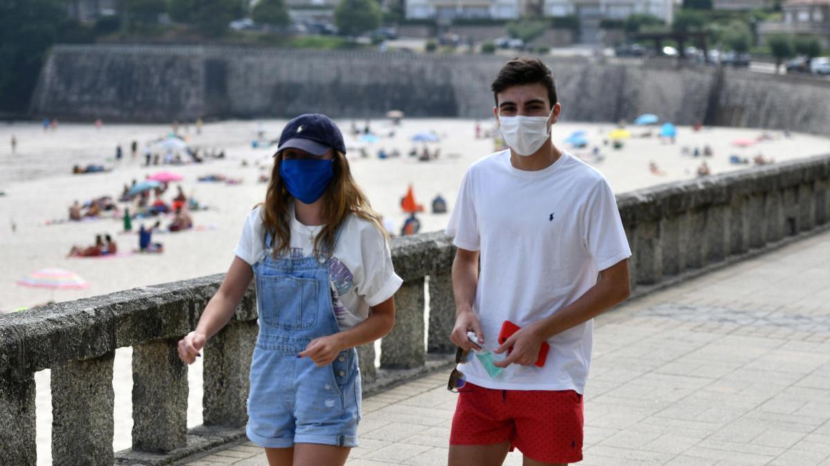 Dos jóvenes con mascarillas por el paseo de la playa de Silgar, en Sanxenxo. // Gustavo Santos