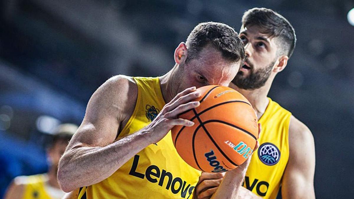 Marcelinho Huertas aprieta el balón contra su cara tras un fallo, mientras es consolado por Santi Yusta.