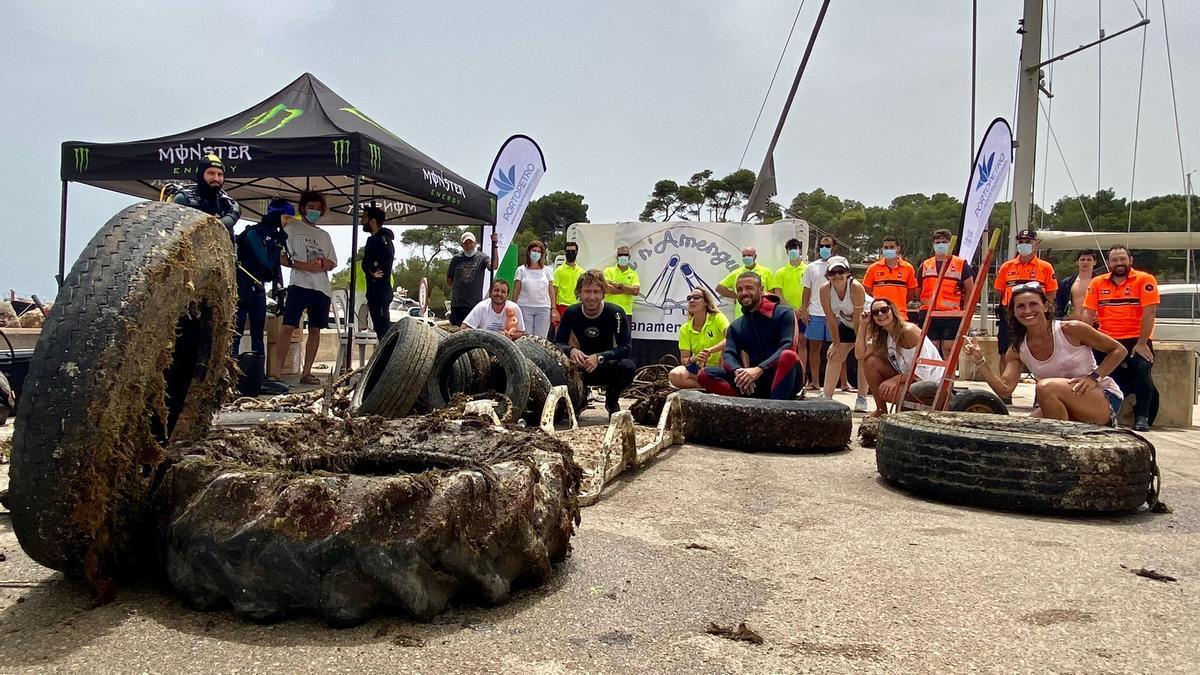 Participantes en la jornada de limpieza posan con algunos de los residuos extraídos del fondo marino.