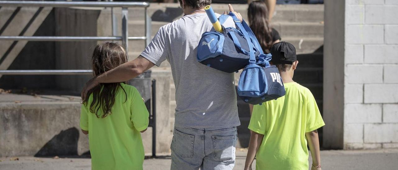 Un padre carga con las bolsas de deporte de sus hijos, en un club deportivo de Barcelona.