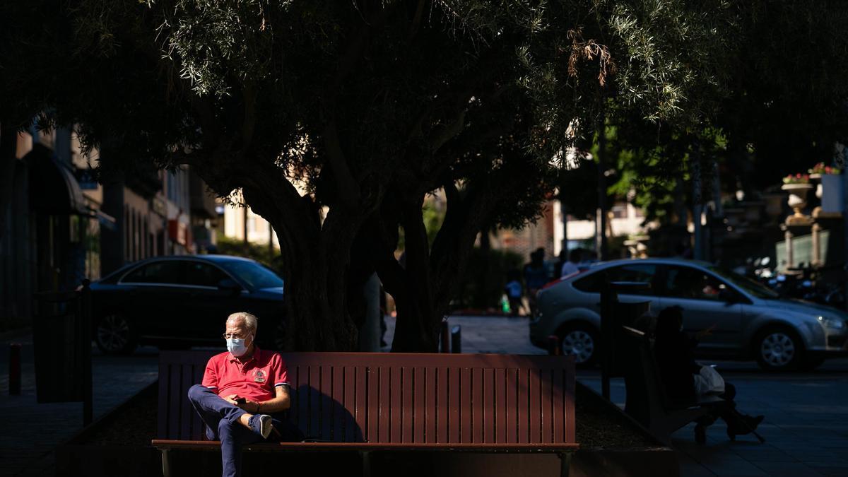 Un hombre con mascarilla para evitar contagios sentado en Santa Cruz de Tenerife.