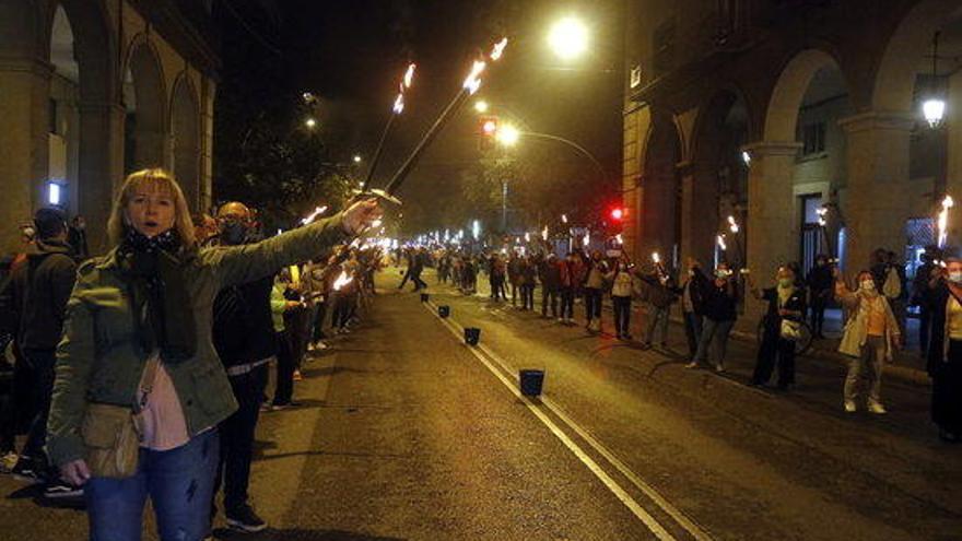 Centenars de persones encenen torxes a Girona per reivindicar l'1-O