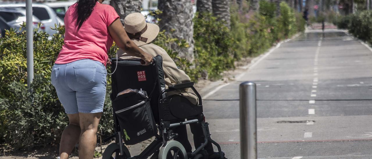 Una mujer lleva en una silla de ruedas a una persona mayor dependiente