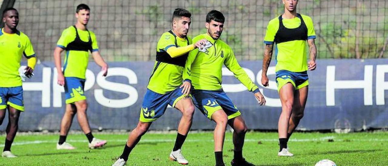 Cristian Cedrés -izqda.- pugna por un balón con Fabio durante el entrenamiento de la UD de ayer en Barrando Seco; detrás, Silva, Clemente y Maikel Mesa .