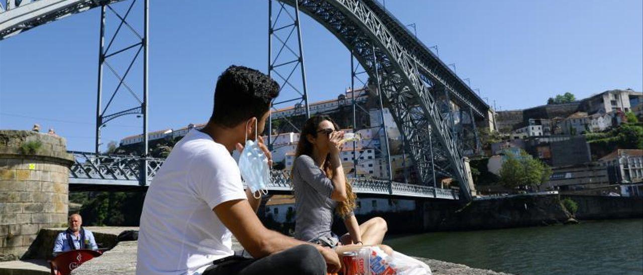 Dos jóvenes bebiendo en el Puente Don Luis I, que une Oporto y Vilanova de Gaia.